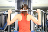 Young woman training with weights in gym
