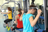 Group of people training with weights in gym