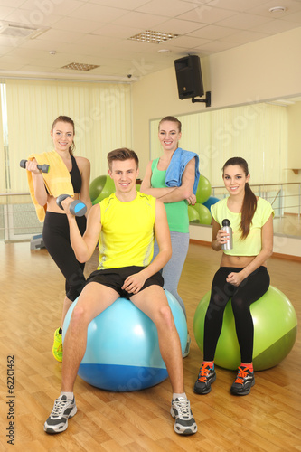 Group of young people with gymnastic ball in gym