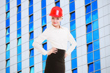 Female engineer woman in red safety helmet and modern building