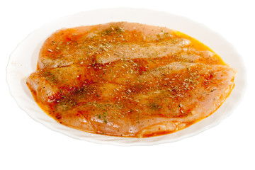 Raw marinated chicken breasts with spices isolated on white
