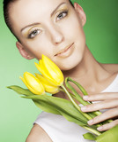 woman with yellow tulips over green background