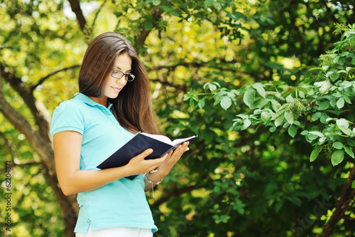 Portrait of attractive young woman with book in a green park