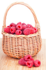 Ripe raspberry in a wattled basket,  on a white background