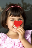 Little girl and red hearts.