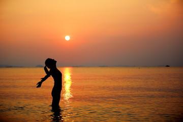 woman open arms sunrise/sunset sea