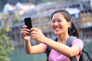 woman tourist use smart phone at fenghuang ancient town,china
