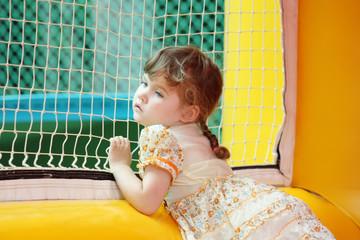 Little beautiful girl in dress stands in bouncy castle an