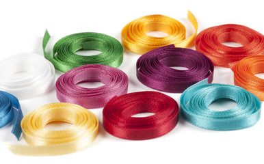 Coiled spools of colorful ribbons on a white background