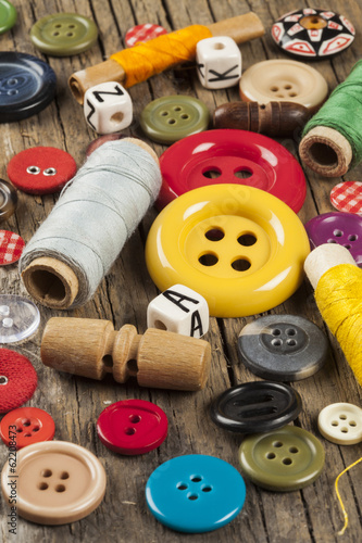 Set of colored sewing buttons on wooden background