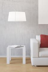 Tisch neben Sofa mit Lampe und Buch