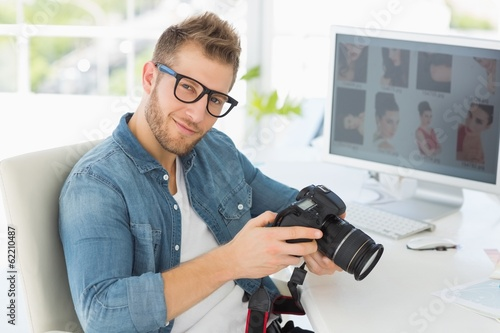 Handsome photographer holding his camera smiling at camera