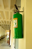 green fire extinguisher on wall in a office environment