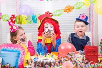 children giving gifts on birthday party with clown