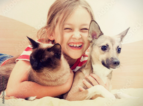 Fototapeta child hugging a cat and dog