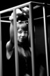Black and white portrait of sexy woman wearing handcuffs in cage