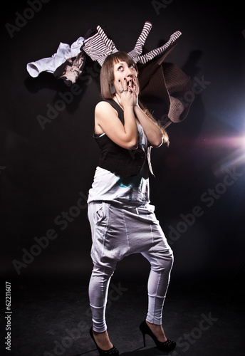 young woman looking with amazement on flying clothes