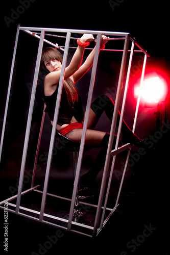 Sexy girl in handcuffs sitting in cage in red light