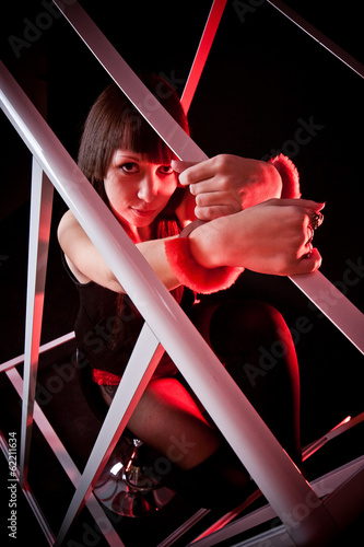 Closeup shot of sexy woman in fasten handcuffs to metal cage