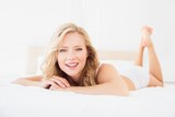 Pretty young blonde smiling at camera on bed