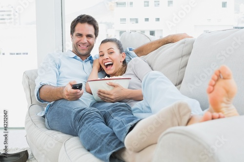 Couple watching funny movie lying on the sofa with bowl of