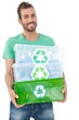Portrait of a smiling young man carrying recycle containers