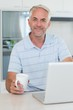 Casual smiling man using his laptop while having coffee