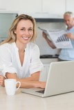 Happy woman using laptop with partner standing with the paper