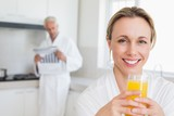 Happy woman drinking orange juice in bathrobe