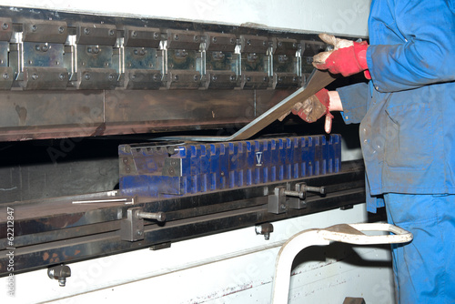 worker operating metal press machine at workshop