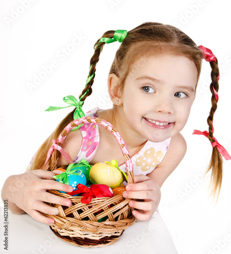 Smiling little girl with basket full of colorful easter eggs iso