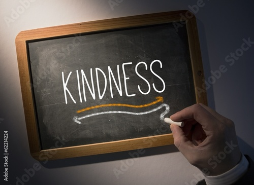Hand writing Kindness on chalkboard