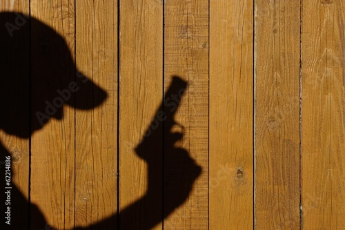Shadow of a man with a gun on a wooden fence, XXXL image