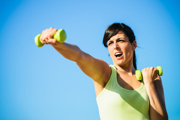 Fitness woman boxing with dumbbells
