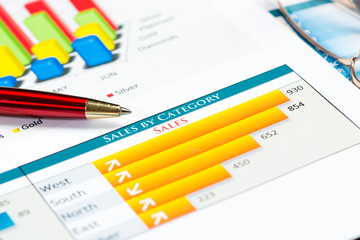close-up of pen and financial growth charts
