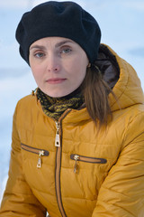 Woman in black beret and yellow jacket
