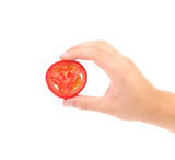 Hand hold slice of tomato.