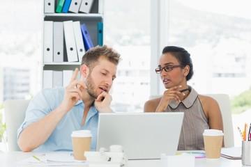 Partners working together at desk on laptop