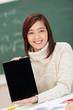 lächelnde asiatische schülerin zeigt tablet-pc