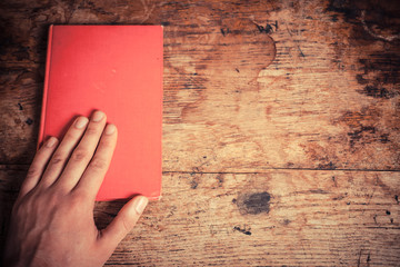 Hand on red book
