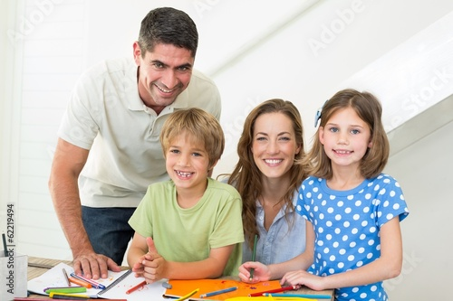 Smiling family coloring at home