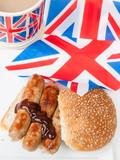 British sausage sandwich with, brown sauce, cup of tea and flag