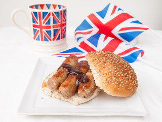 English sausage sandwich with, brown sauce, cup of tea and flag