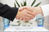 businessman and businesswoman shaking hands over signed contract