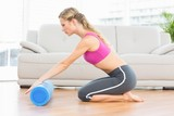 Fit blonde kneeling on floor using foam roller
