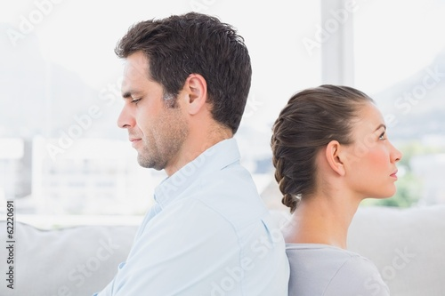 Unhappy couple sitting back to back on the couch