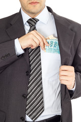 A businessman in a suit putting brazilian money in his pocket