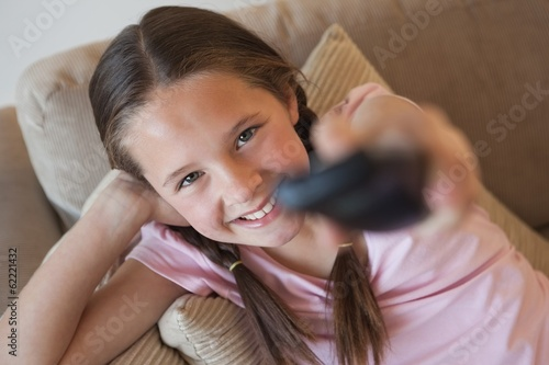 canvas print picture Portrait of a girl changing channels in living room