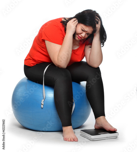 Overweight woman with a weighing machine and measure tape.