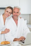 Smiling couple using laptop at breakfast in bathrobes